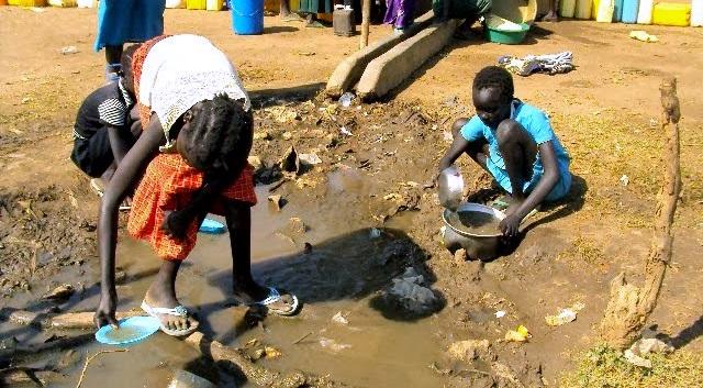 Flyktninger henter vann fra en vannhull utenfor Dzaipi i Uganda, på grensen til Sør-Sudan. Det er lite vann i flyktningleiren. Foto: CARE